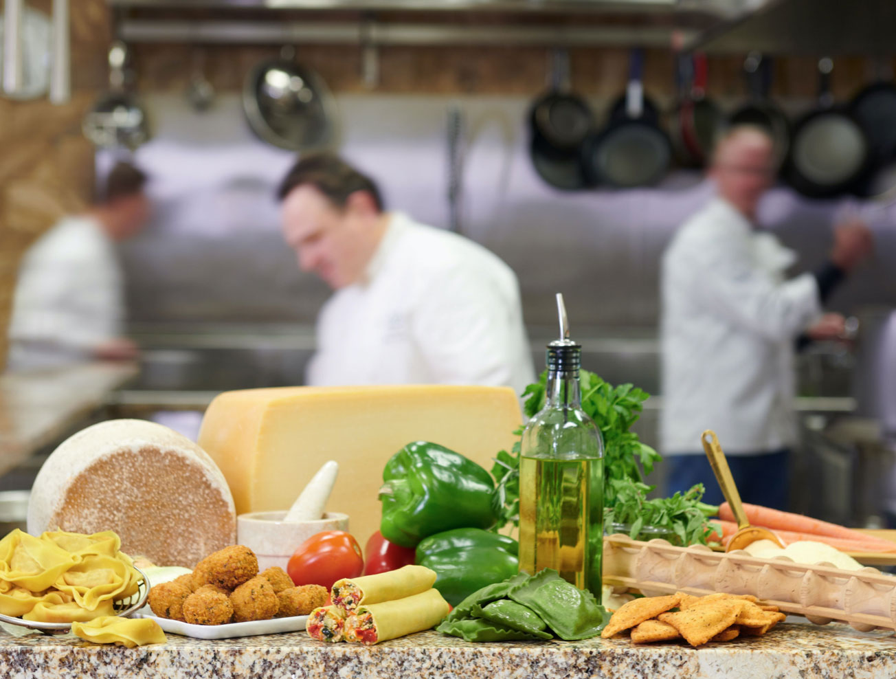 Ingredients displayed on a table with chefs cooking in the background